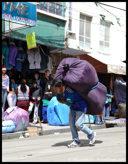 Un homme transportant des marchandises à même le dos sur un marché de La Paz